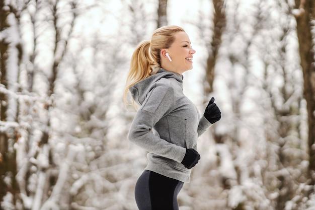 눈 덮인 겨울 날에 숲에서 조깅하는 행복 맞는 sportswoman. 건강한 라이프 스타일, 겨울 스포츠