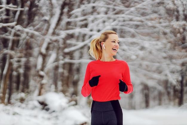 눈 덮인 겨울 날 숲에서 조깅을 하는 행복한 스포츠우먼. 야외 피트니스, 겨울 피트니스, 건강한 라이프 스타일