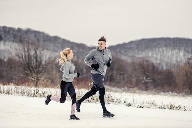 雪の降る冬の日に自然の中で走っているハッピーフィットのスポーティなカップル。アウトドアフィットネス、健康的な生活、冬のフィットネス