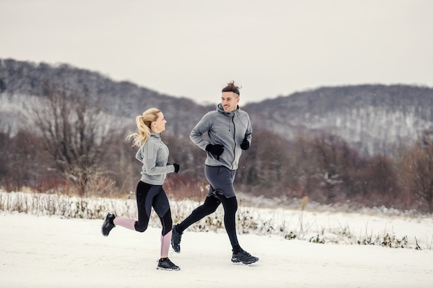 Happy fit sporty couple running in nature at snowy winter day. outdoor fitness, healthy life, winter fitness