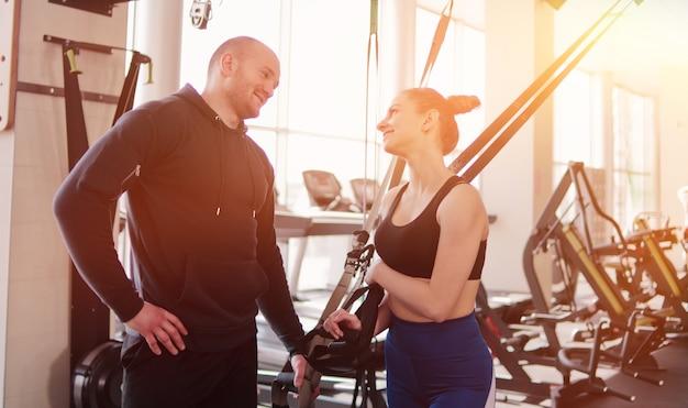 フィットネスストラップで運動からの休憩中に話している幸せなフィットの女性と男性