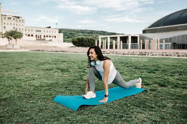 都市公園で屋外のストレッチの日ルーチンをしている幸せなフィットの女性