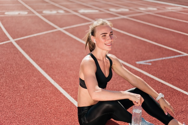 Happy fit woman in sportwear listening to music with earphones and holding water bottle while sitting on a stadium track with red coating outdoor. running,