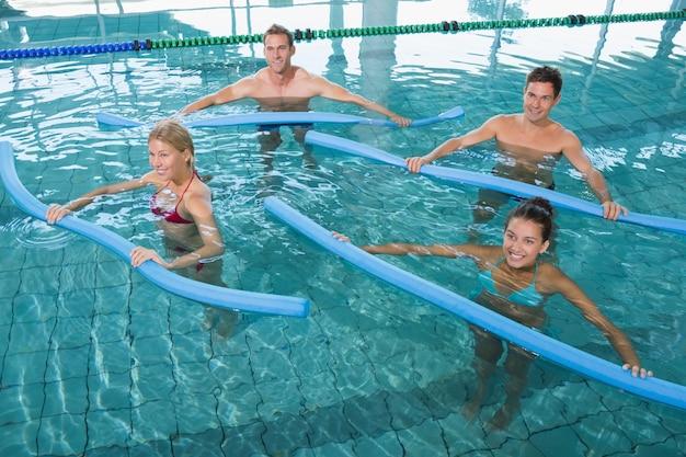 Happy fitness class doing aqua aerobics with foam rollers