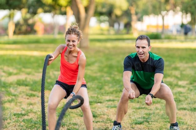 공원에서 여자와 훈련하고 전투 로프를 사용하는 행복한 피트니스 코치.