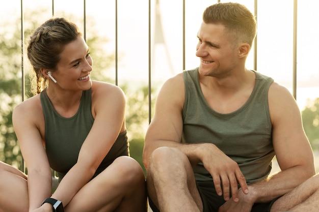 Счастливая пара фитнеса после тренировки на улице во время заката