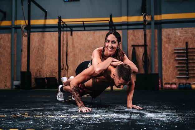 근육을 늘리기 위해 체육관에서 열심히 운동하는 30대 소년과 소녀의 행복한 피트니스 커플
