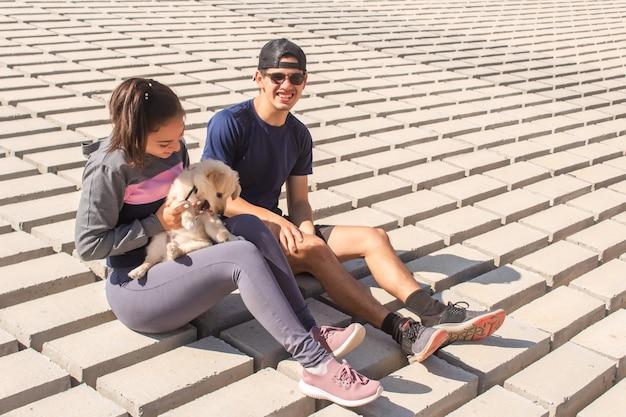 海岸で子犬と遊ぶ幸せなフィットネスカップル。
