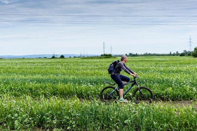 幸せなフィットネス女の子は夏の日に緑の野原を渡って自転車に乗っています。