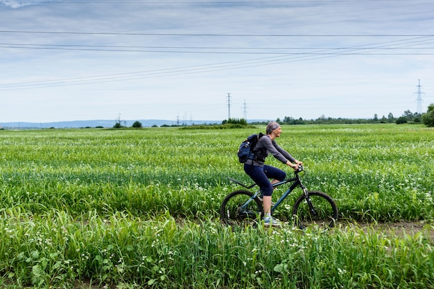 Happy fitness girl is riding a bicycle across the green field at summer day