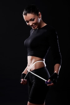 Happy fitness girl measuring her waistline
