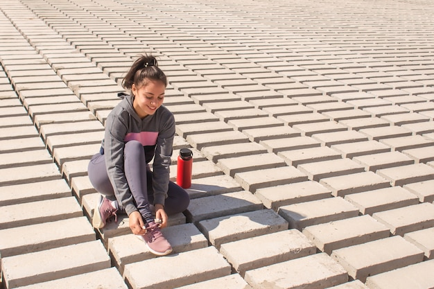 海岸で靴ひもを結ぶ幸せなフィットネスの女の子。