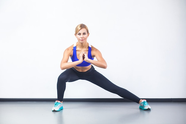 Happy fitness woman doing stretch exercising, looking at camera. studio shot