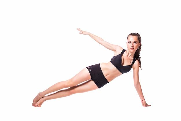 Felice fitness donna facendo esercizi di stretching isolati su uno sfondo bianco.