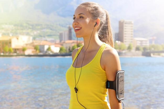健康的なライフスタイルに合う幸せなフィットネス女性。電話とイヤホンのアクティブウェアとスポーツアームバンド、背景にランニングまたはカーディオトレーニング市湖のハイテク機器を身に着けている若い女の子。
