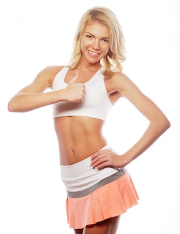 Happy fitness woman showing thumb up