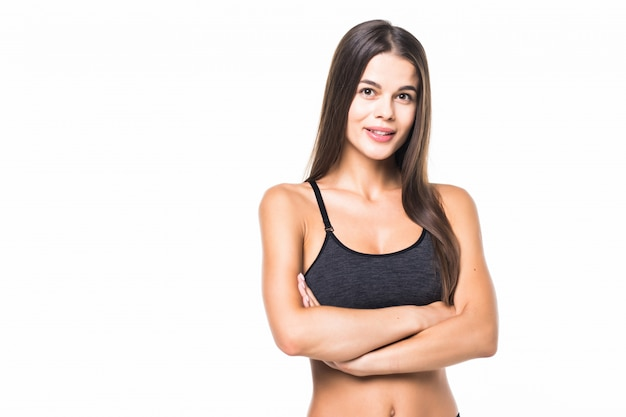 Happy fitness woman standing with arms folded on white