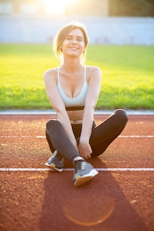 Happy fitness woman wears fashionable sportswear sitting on the running track