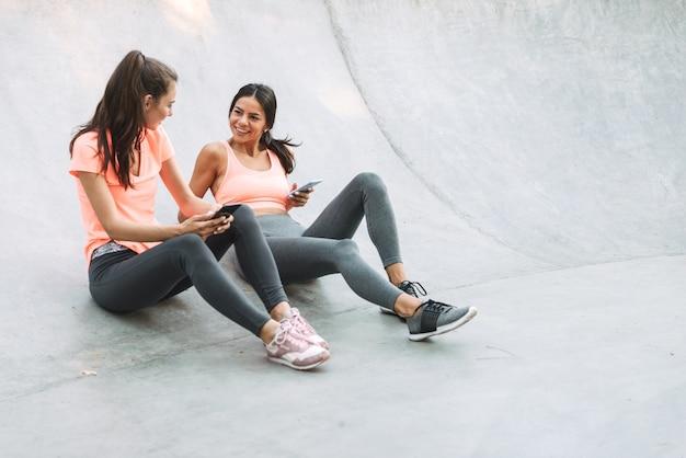 콘크리트 운동장에 앉아있는 동안 미소하고 핸드폰을 함께 들고 운동복에 행복한 피트니스 여성