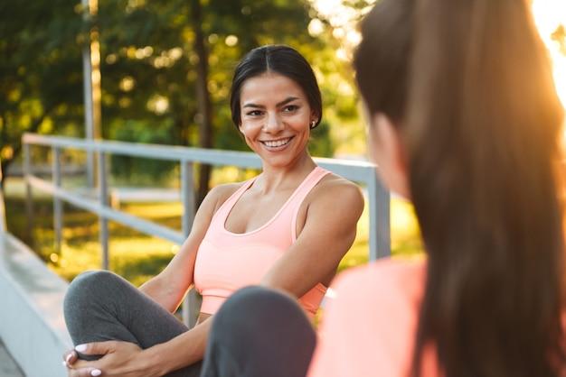 녹색 공원에 앉아있는 동안 웃고 함께 이야기하는 운동복에 행복한 피트니스 여성
