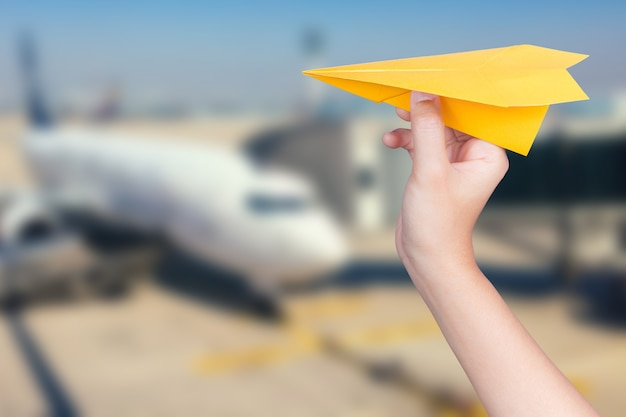Счастливая концепция полета с рукой, держащей бумажный самолетик с самолетом размытым фоном
