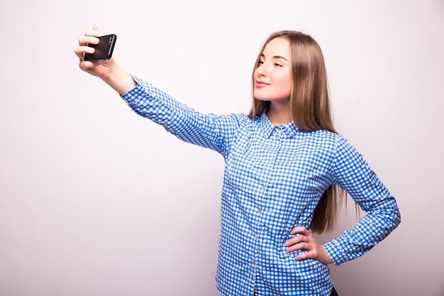 흰 벽 위에 스마트 폰에서 자신의 사진을 찍는 행복 유혹 어린 소녀
