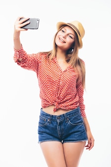 Happy flirting young woman taking pictures of herself through cell phone, over white background