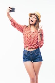 흰색 배경 위에 휴대 전화를 통해 자신의 사진을 찍고 행복 유혹 젊은 여자