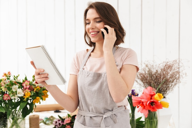 Happy florist woman in apron working in flower shop, and speaking on cell phone while holding notes in hand