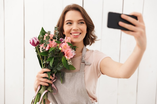 Happy florist woman standing with flowers make selfie by mobile phone.