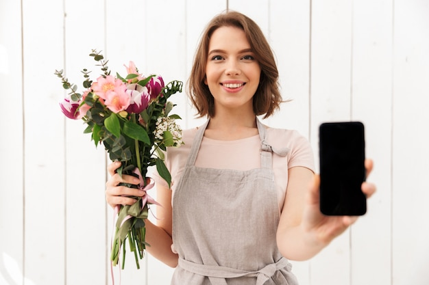 Happy florist woman standing with flowers showing display of mobile phone.