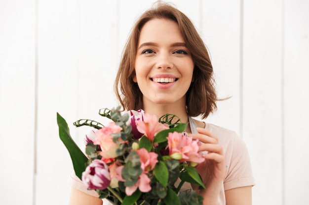 Happy florist woman standing with flowers
