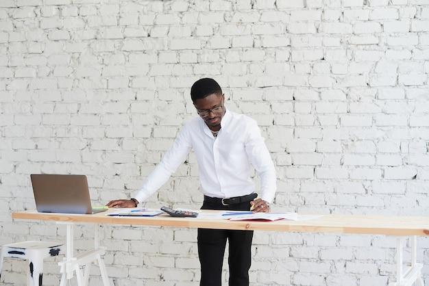 Счастливый сосредоточенный афроамериканец разговаривает по видеосвязи с партнерами-клиентами. молодой темнокожий мужчина использует ноутбук в современном офисе.
