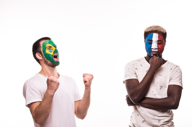 Appassionato di calcio felice del brasile festeggia la vittoria sul tifoso sconvolto delle squadre nazionali di francia con la faccia dipinta isolato su priorità bassa bianca