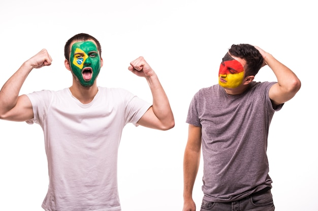 Happy football fan of brazil celebrate win over upset football fan of germany national teams with painted face isolated on white background