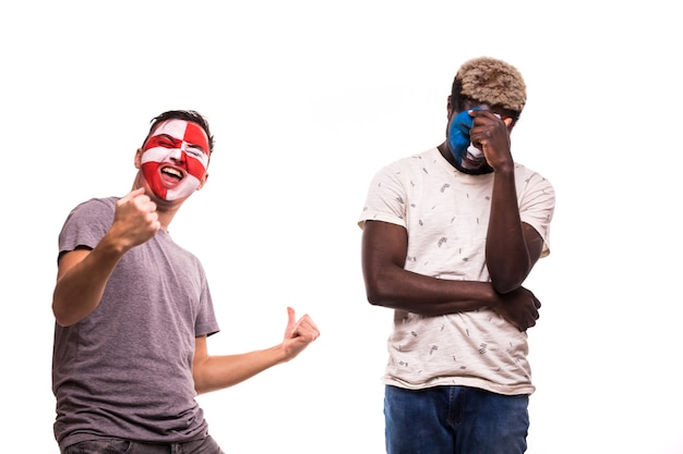 Happy football fan of croatia celebrate win over upset football fan of france with painted face isolated on white background