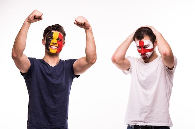 ベルギーの幸せなサッカーファンは、白い背景で隔離の塗られた顔でイギリスの動揺したサッカーファンの勝利を祝う