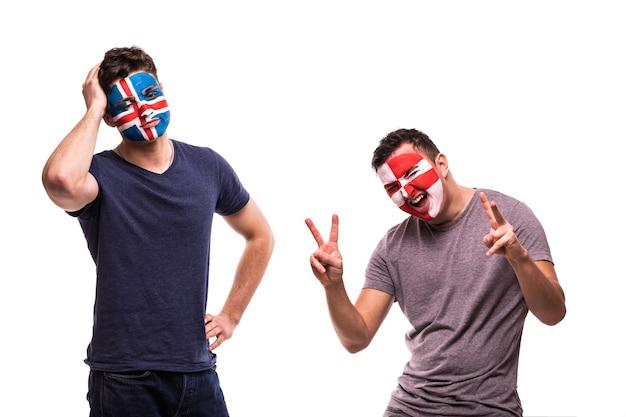Счастливый футбольный болельщик хорватии празднует победу над расстроенным футбольным фанатом исландии с раскрашенным лицом