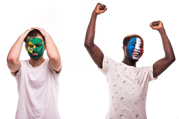 Счастливый футбольный фанат франции празднует победу над расстроенным футбольным фанатом сборных бразилии с раскрашенным лицом, изолированным на белом фоне