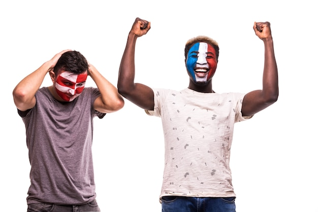 フランスの幸せなサッカーファンは、白い背景で隔離の塗られた顔でクロアチアの動揺したサッカーファンの勝利を祝う