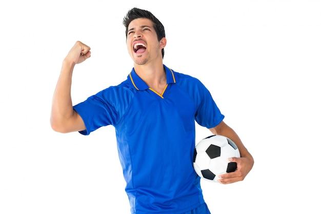 Счастливый футболист в синем праздновании
