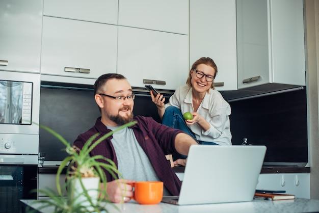 家庭の台所で一緒に時間を過ごす幸せな40歳の夫婦。男性はノートパソコンを見てモニターを指さし、眼鏡をかけた女性は後ろに座って笑います。妻に焦点を当てます。