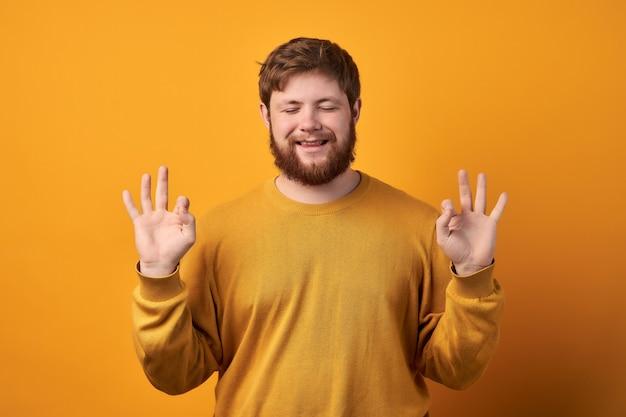 Счастливый, ловкий молодой мужчина с довольным выражением лица, делает нормальный жест, закрывает глаза от счастья, одет в повседневную белую футболку, носит повседневную одежду