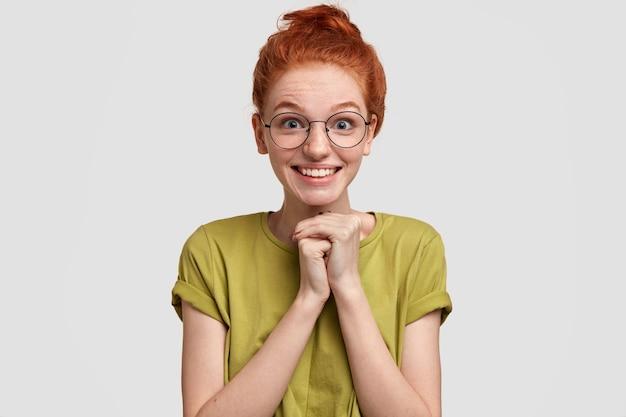 Счастливая веснушчатая рыжая женщина с позитивной улыбкой держит руки вместе, ожидает чего-то удивительного, носит повседневную футболку