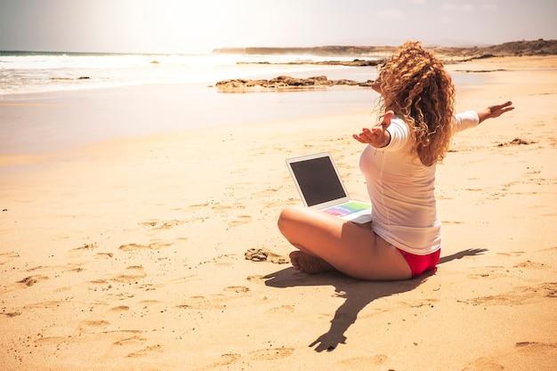 幸せな自由な人々の白人女性は、休暇の夏と市内のストレスオフィスから解放された仕事のための自由を楽しんでいる彼女の足にコンピューターのラップトップを持ってebachに座っています