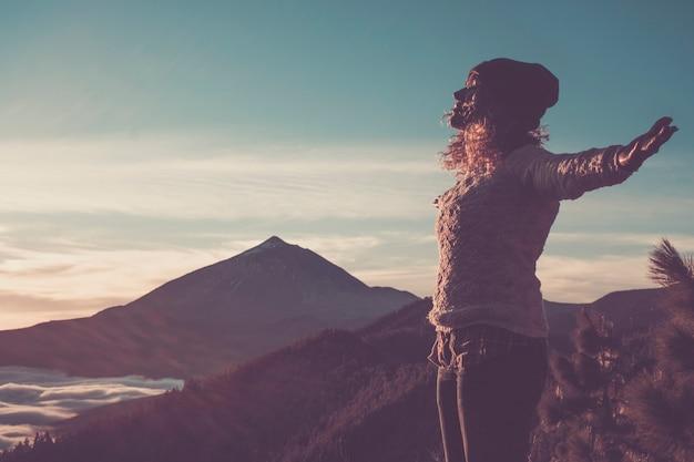 幸せな無料の女性が腕を広げて、山で驚くほど美しい夕日をお楽しみください-アクティブな人々と屋外のレジャー活動-ハイカーの女性の大人と背景の風景の景色