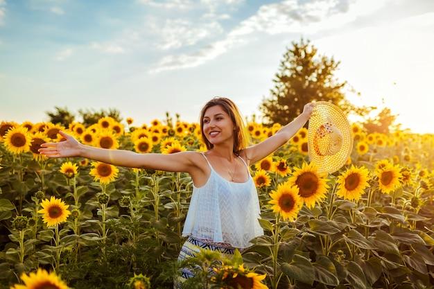 幸せな自由な女は、麦わら帽子を保持している咲くひまわり畑を歩いて腕を開いた。
