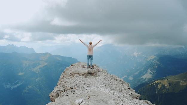Счастливая свободная женщина с протянутыми руками на вершине скалы. наслаждаясь природой и чувствуя себя свободным.