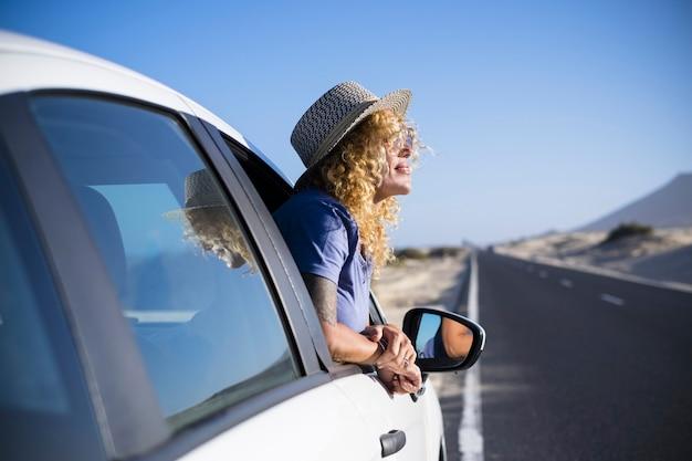 美しい孤独な旅行者の大人の白人女性と幸せな自由の概念は、彼女の白い車の窓の外で旅行のライフスタイルをお楽しみください