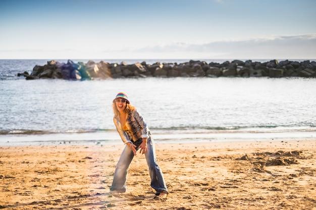 Счастливая свобода сумасшедшая женщина среднего возраста прыгает на пляж для счастья и радости жизни на открытом воздухе каникулы лето океан и пляж концепция